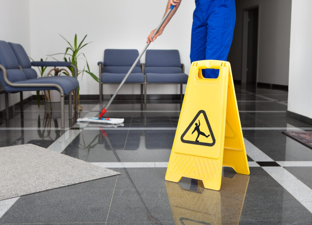 janitor mopping wet floor next to a customized safety signage